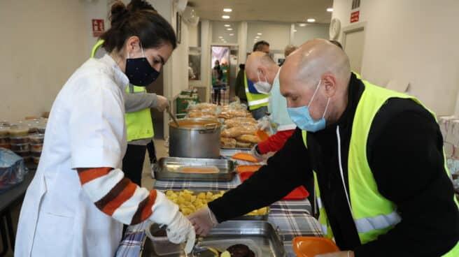 Una cocinera sirve comida varias raciones de comida a voluntarios