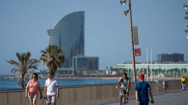Una pareja pasea sin mascarilla por la Barceloneta.