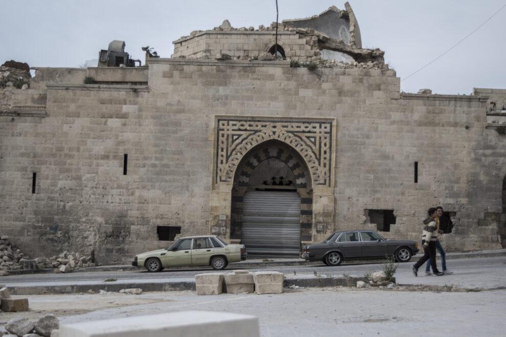 Unos jóvenes pasean por las ruinas de Alepo viejo
