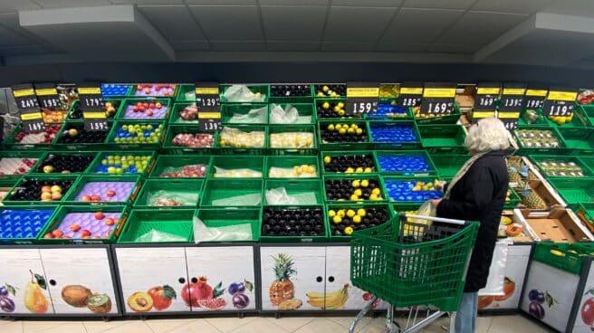 Un mujer coloca fruta en una bolsa mientras observar los productos que quedan en las cajas de un supermercado.
