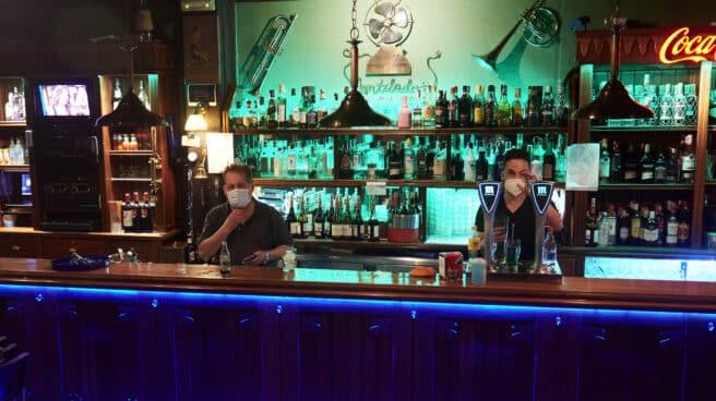 Dos camareros en un local de ocio nocturno, antes de su cierre a medianoche en Santander