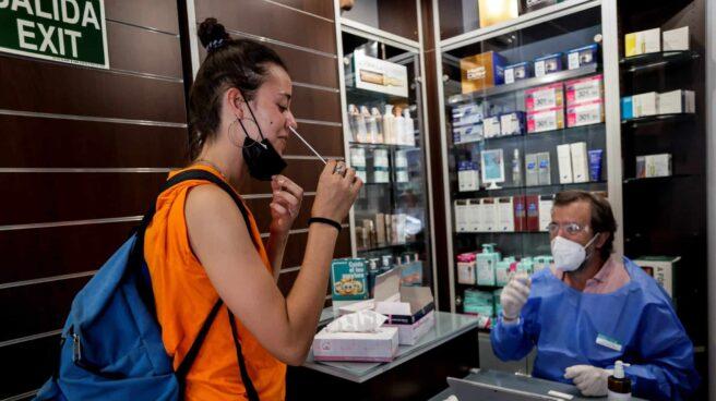 Chica realizándose un test de antígenos de autodiagnóstico en una farmacia junto a un farmacéutico