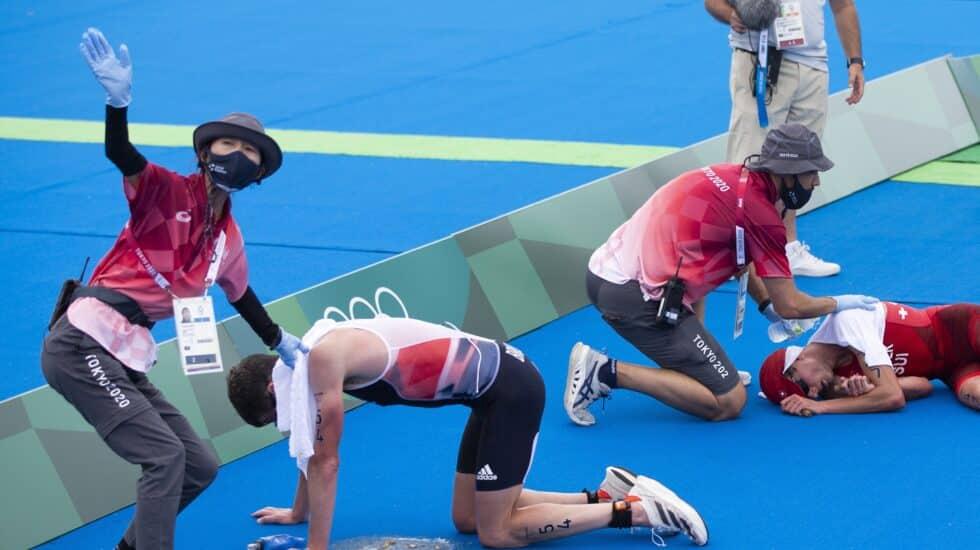 Dos triatletas, exhaustos en la llegada a meta en Tokio 2020