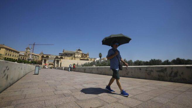 Un hombre se resguarda del sol bajo un paraguas mientras camina por el Puente Romano de Córdoba.