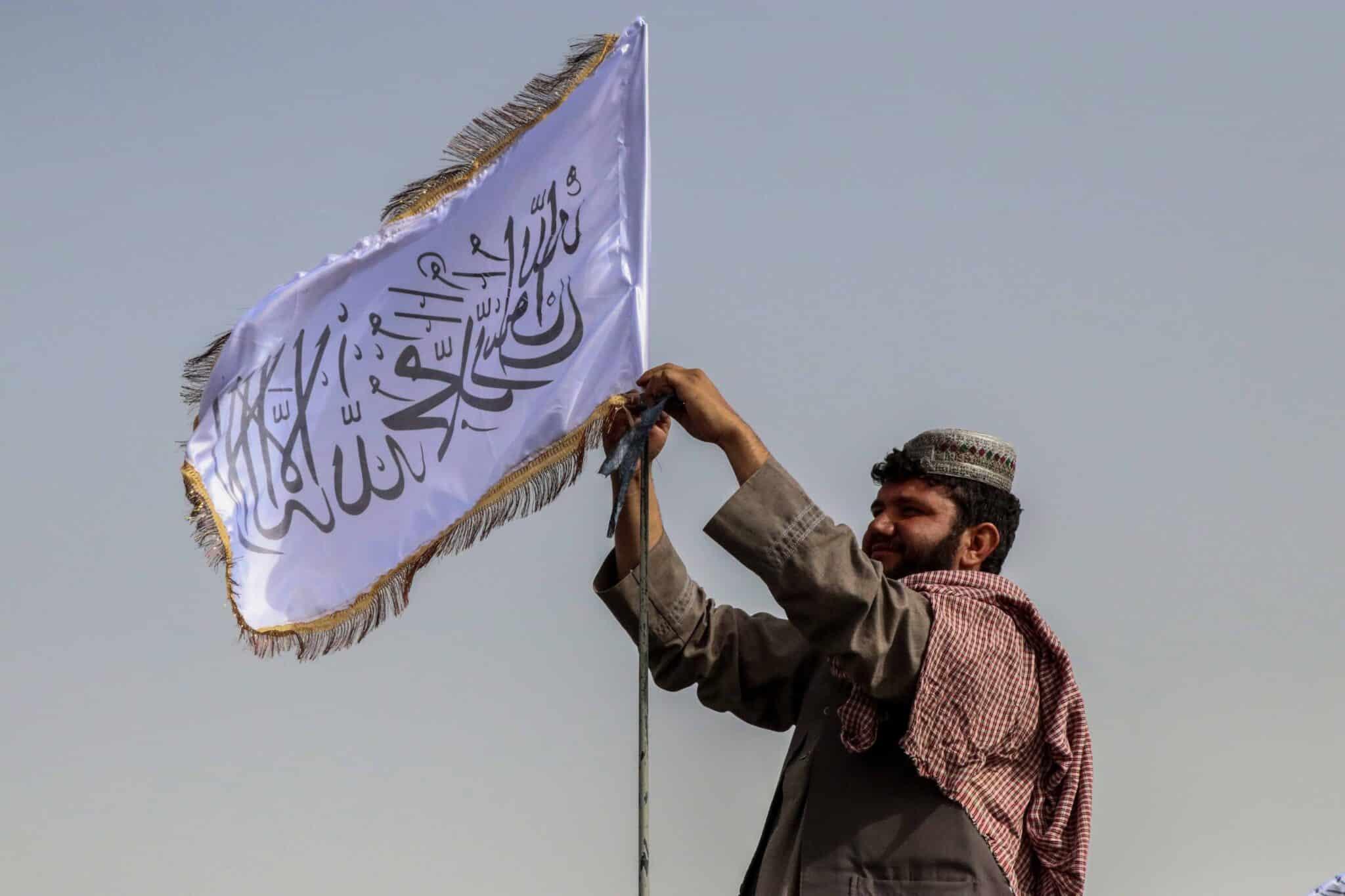 Un talibán coloca la nueva bandera de Afganistán en Kandahar