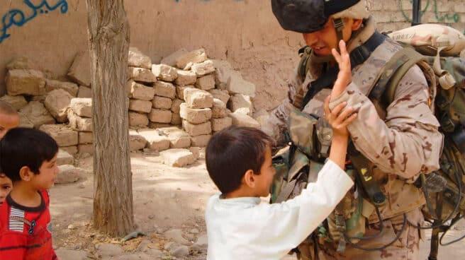 Unos niños juegan con un soldado español en Badghis, en 2010