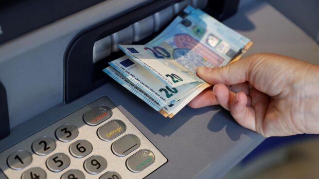 Una persona saca dinero de un cajero de una entidad bancaria.