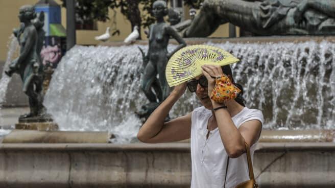 Una mujer se tapa la cabeza con un abanico para guarecerse de las altas temperaturas en Valencia.