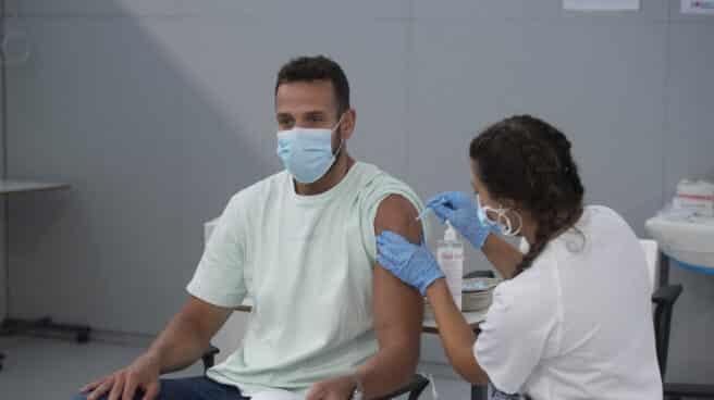 Un joven recibe la primera dosis de la vacuna Pfizer en el Hospital Zendal