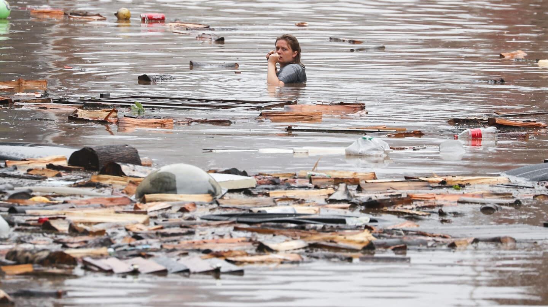 una mujer atraviesa una calle inundada en belgica