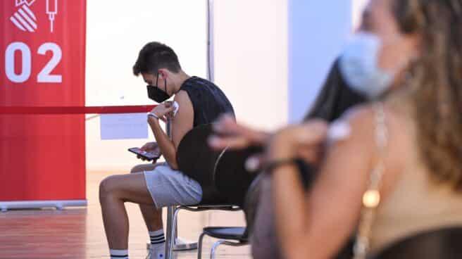 Un adolescente espera en una sala, después de recibir la primera dosis de la vacuna Pfizer en el punto de vacunación de Xátiva, Valencia.