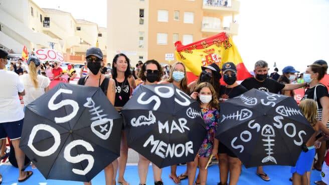 Varias personas participan en una protesta en defensa del Mar Menor.