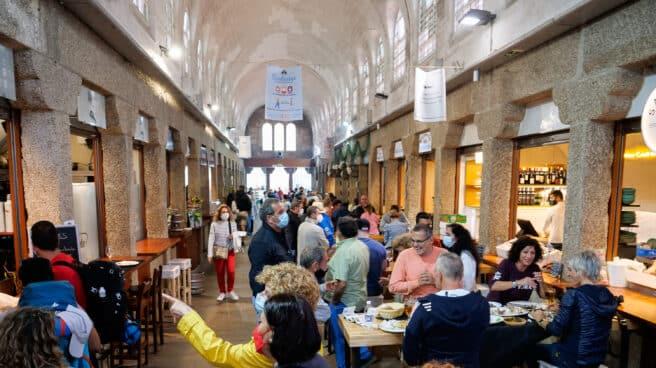 Varias personas acuden a un espacio con locales de hostelería en Santiago de Compostela, A Coruña.