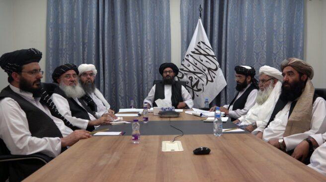 El mulá Abdul Ghani Baradar, junto a la bandera, talibán en una reunión