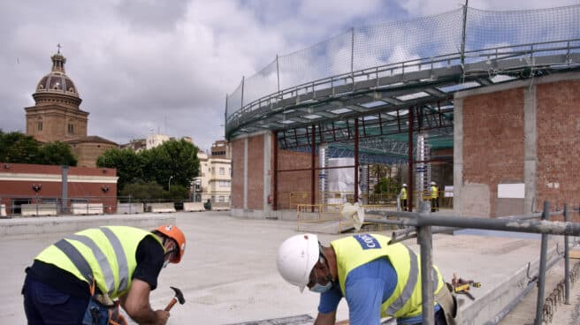 Dos obreros trabajan en las obras de construcción de la nueva estación subterránea de Sant Andreu Comt en Barcelona.
