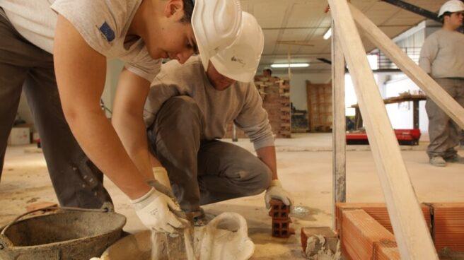 Dos albañiles preparan una mezcla de cemento.