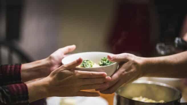 dos personas se pasan un plato con comida saludable