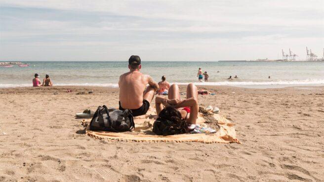 Dos personas en la arena en una playa observando el mar