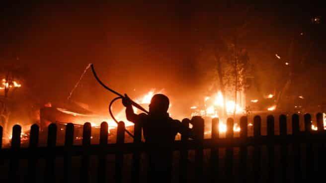 Un hombre intenta extinguir un fuego en Varybobi, un suburbio de Atenas.