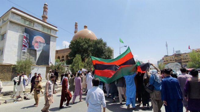 Afganos marchan por Kabul, frente a un mural del presidente huido Ghani, durante el Día de la Independencia.