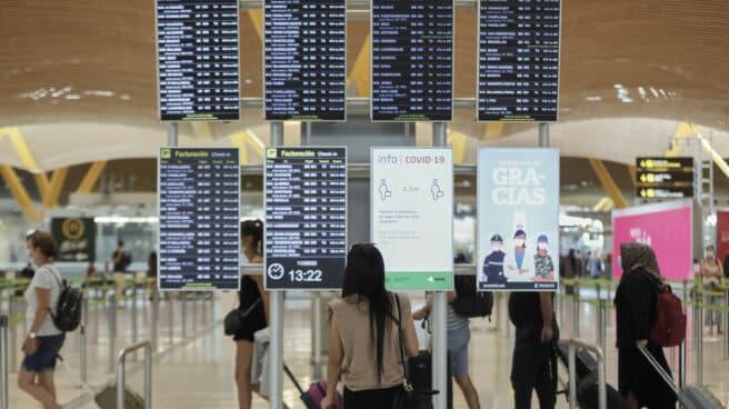 Pasajeros cerca de páneles informativos en la terminal T4 del aeropuerto Adolfo Suárez Madrid-Barajas.