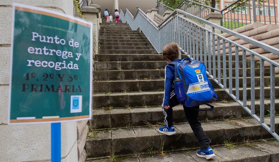 Un niño entra en un colegio.