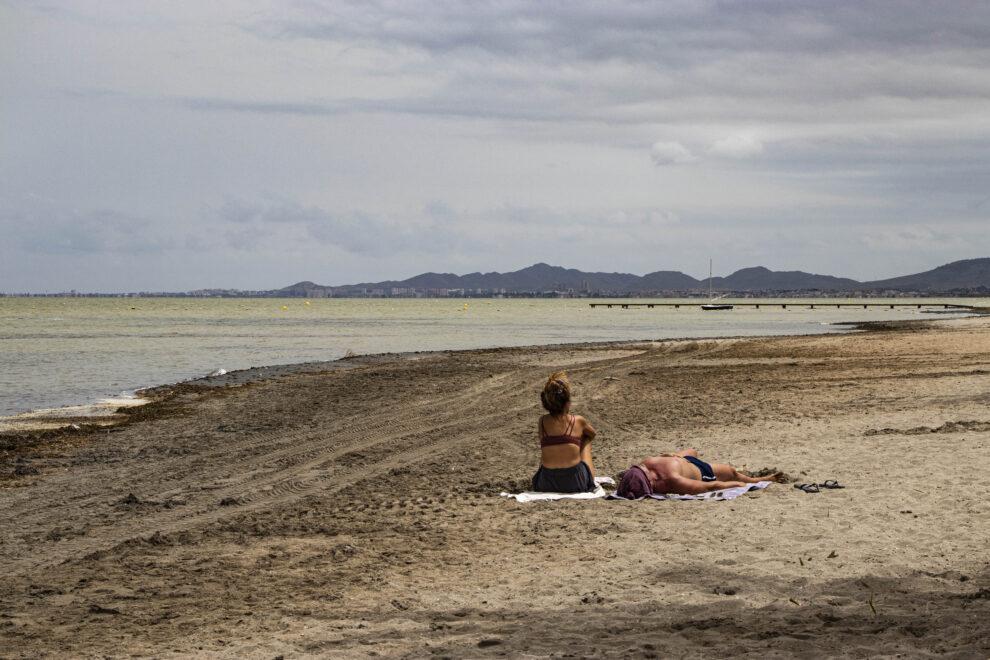 Dos bañistas toman el sol en la playa de Los Urrutias.