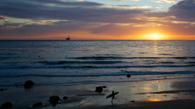 Un surfista en la orilla de una playa en la puesta de sol.