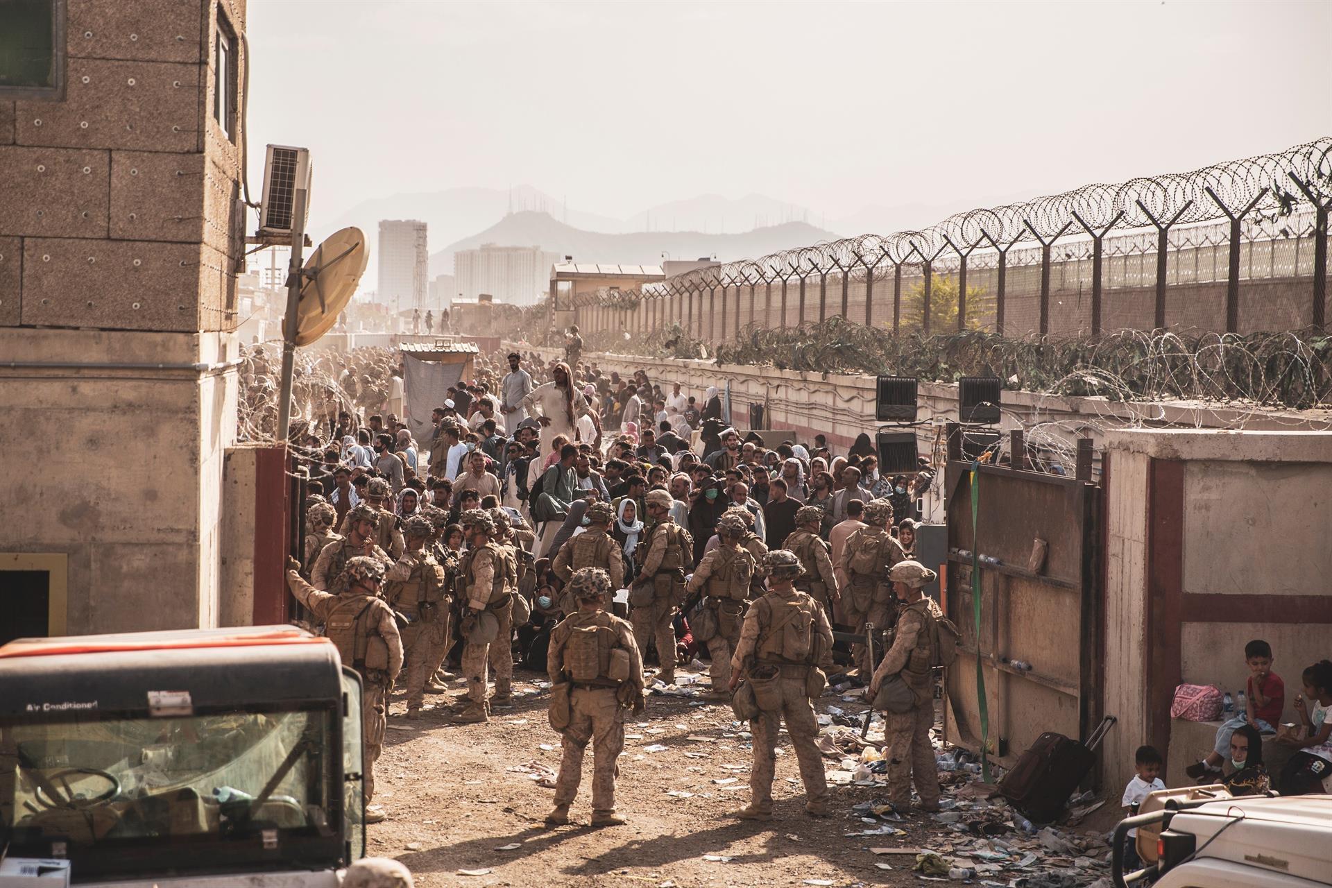 Soldados norteamericanos con ciudadanos afganos en el aeropuerto internacional de Kabul.