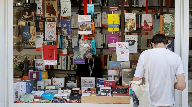 Un hombre se interesa por un libro en la Feria del Libro de Madrid.