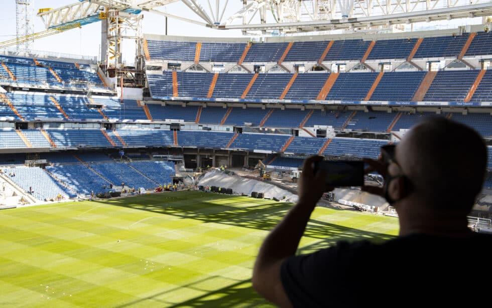 Un aficionado saca una fotografía desde la grada abierta al Tour del Bernabéu
