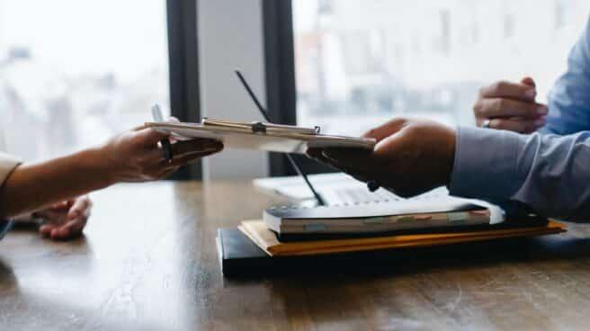 Un candidato entrega su currículum en una entrevista de trabajo