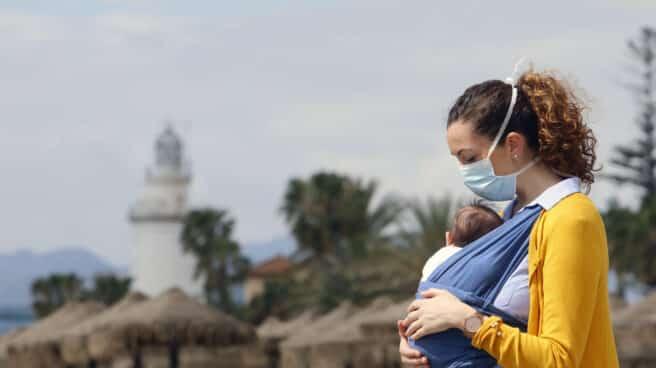 Una mujer protegida con una mascarilla da un paseo con su bebé en la playa de La Malagueta en abril de 2020.