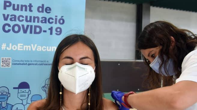 Mujer con mascarilla siendo vacunada por una sanitaria contra el Covid-19