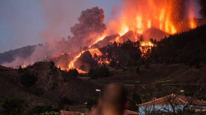 Imagen del Volcán de La Palma en plena erupción y una persona tomando fotografías del momento
