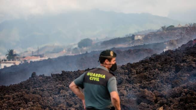 Un guardia civil vigila la lava del volcán de La Palma.