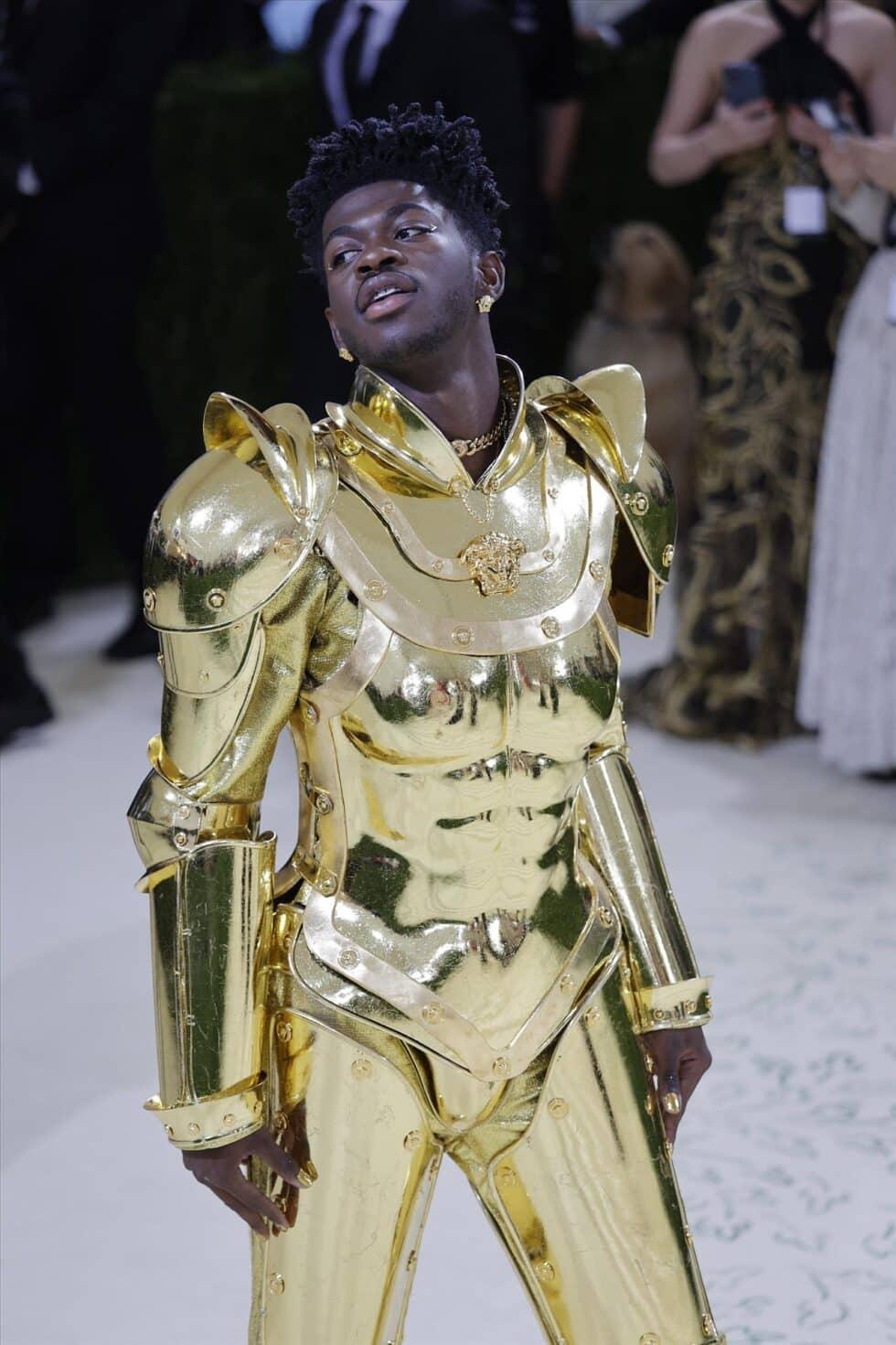 El cantante Lil Nash X ha presentado tres conjuntos a su llegada al evento, todos ellos en color oro y diseñados por Donatella Versace