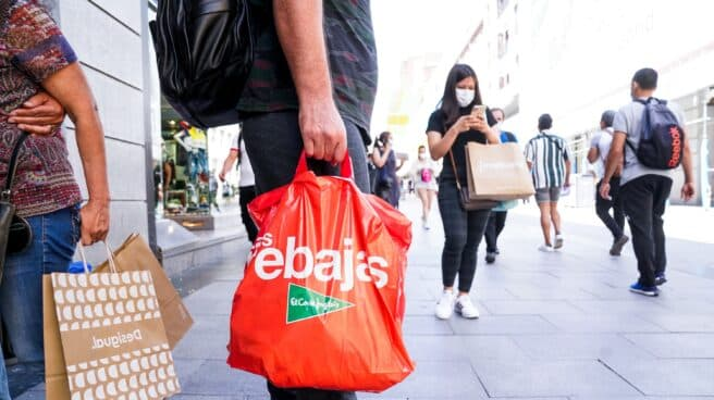 Un hombre sostiene varias bolsas en plenas rebajas de verano en Madrid.