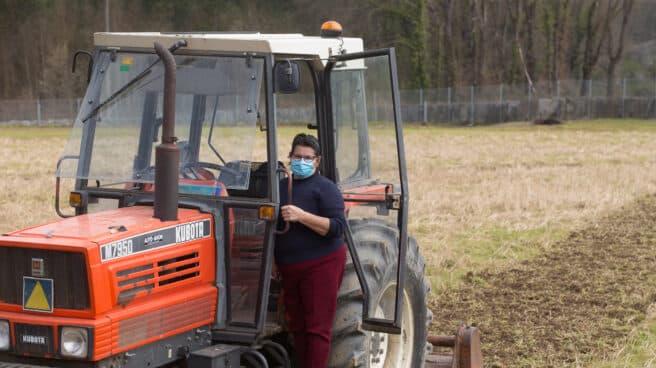 Una mujer, Lola Martínez ara con marcarilla en su tractor para plantar patatas en su finca de Chamoso, O Corgo, en Lugo, Galicia (España).