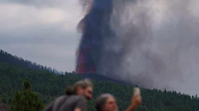 Varias personas observan la actividad de la erupción volcánica.