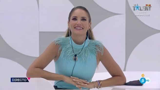 Alba Carrillo sentada en una mesa y sonriendo a cámara