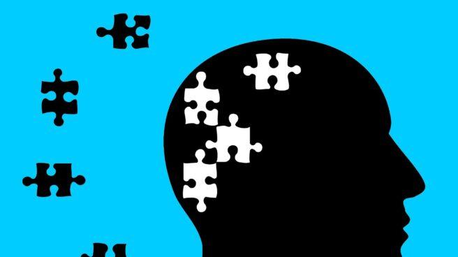 Ilustración de la silueta de la cabeza de perfil de un hombre sobre fondo azul con piezas de puzzle para referenciar las alteraciones que produce el Alzheimer