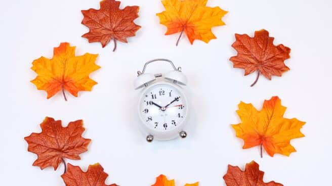 Imagen de archivo de un reloj rodeado por hojas de otoño en referencia al cambio de hora de invierno