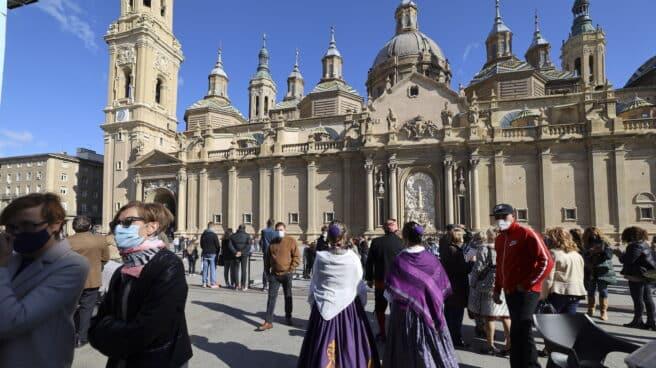Varias personas vestidas de maños se concentran en las inmediaciones de la Basílica del Pilar