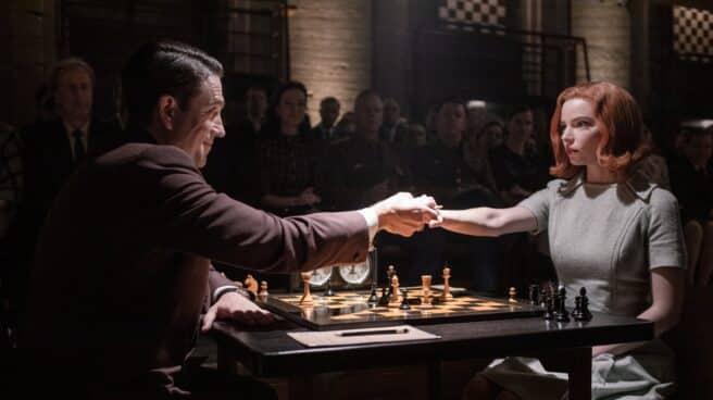 Actores de la serie de Gambito de Dama dandose la mano en una mesa de ajedrez