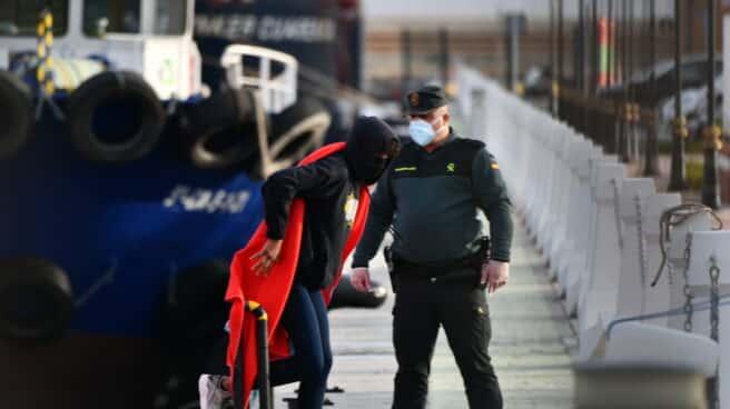 Un agente de la Guardia Civil ayuda a desembarcar a migrantes en Ceuta.