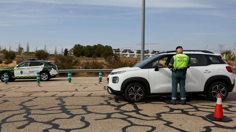 Un guardia civil de Tráfico pide la documentación a un conductor en un control de carretera.