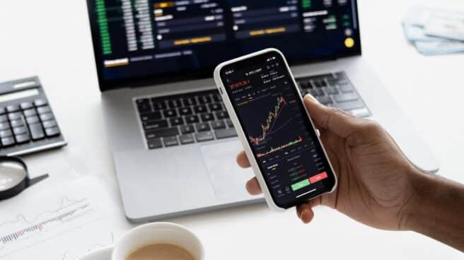 Un hombre consulta sus inversiones en la pantalla de su teléfono móvil.