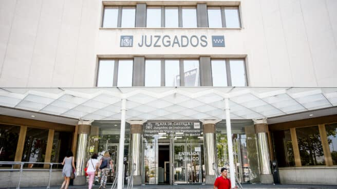 Personas entran por la puerta de los Juzgados de Instrucción ubicados en la Plaza de Castilla de Madrid.