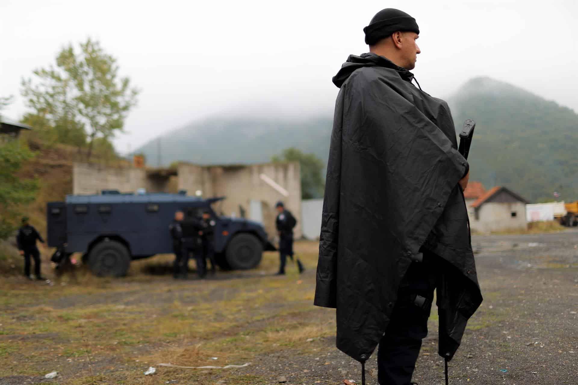 Un policía kosovar, con chubasquero y arma automática.